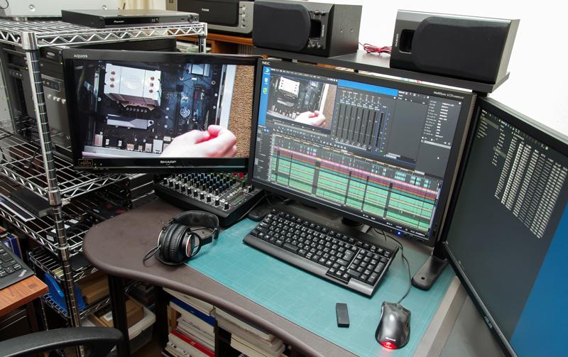 私は編集作業を行うデスクを2か所に持っていますが、この写真はそのうちの1つ。中央と右のディスプレイはPCのディスプレイで、編集ソフトのウィンドウを中心に広げます。左のディスプレイはTVで、画面の出力状態をリアルタイムで確認するために使います。左のディスプレイの奥に、編集用PCを3台並べてあり、モニターとキーボード、マウスを切り替えながら使います。音の編集と色の細かい調整はこちらのデスクではやらないので、音はヘッドフォンで聴いて確認に使う程度です